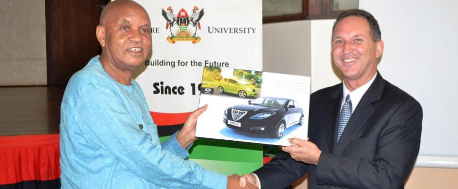 The Chancellor Prof. George Mondo Kagonyera (L) hands over a souvenir of the Kiira EV SMACK to outgoing Israel Ambassador H.E. Gil Haskel during his farewell visit to Makerere University, Kampala Uganda on 14th July 2014