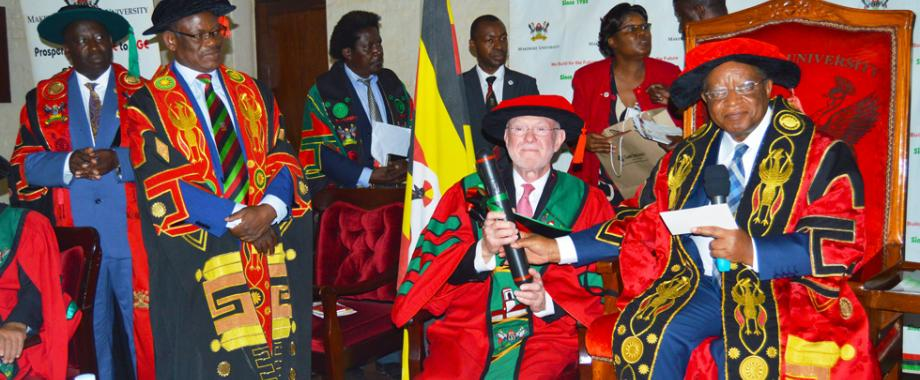Dr. David Poplack, Professor of Pediatrics at Baylor College of Medicine receives a cylinder from the Chancellor Prof. Ezra Suruma (Right) at a special graduation ceremony held on 9th August 2018 in the Main Hall. Looking on is the Vice Chancellor Prof Barnabas Nawangwe (Standing 2nd Left) and Principal College of Health Sciences - Prof. Charles Ibingira (Extreme Left)