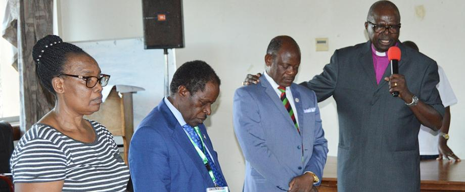 Bishop Henry Luke Orombi (Right) praying for Vice Chancellor Prof. Barnabas Nawangwe at the meeting with Lecturers, Deans and Top Management held at Senate Conference Hall, Level 4 on Friday, 21st September 2018. Ag. Deputy Vice Chancellor Prof. William Bazeyo (2nd Left) and University Librarian Dr Hellen Byamugisha (Left) among others were present.