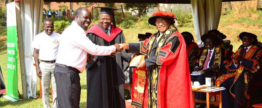 The Chancellor-Prof. Ezra Suruma (R) shakes hands with Chairman Convocation-Dr. Odoi Tanga (2nd L) as Principal CAES-Prof. Bernard Bashaasha (2nd R) and MUASA Chairman & Convocation PRO-Dr. Kamunyu Muhwezi (L) witness, 16th January 2018, Makerere University, Kampala Uganda. Prof. Bashaasha received the best overall science student award plaque and UGX1million from Makerere University Convocation on behalf of Mr. Odongo Brian Boniface-BSc. Food Science and Technology.