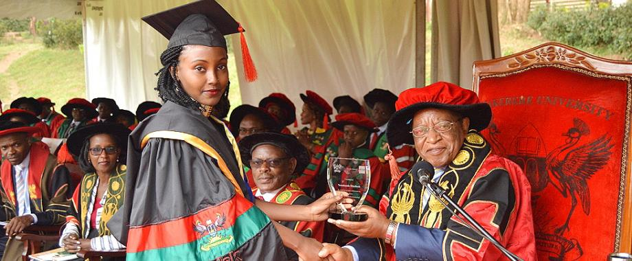 The Chancellor, Prof. Ezra Suruma (Right) hands over the ACCA Uganda Award to Ms. Tumukunde Elizabeth, the best performing student in Bachelor of Commerce (Accounting Option) during the 2nd Session of the 69th Graduation Ceremony at Makerere University, Kampala Uganda
