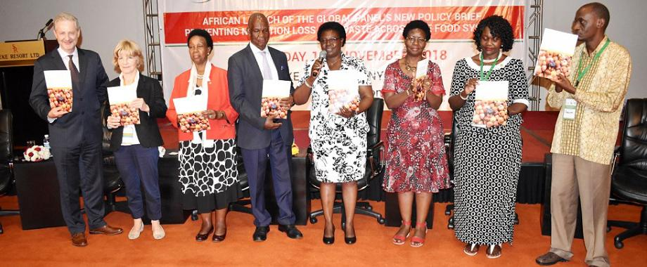 Hon. Grace Freedom Kwiyucwiny (4th R) flanked by Dr. Wilberforce Kisamba Mugerwa (4th L), H.E. Rhoda Peace Tumusiime (3rd L), Prof. Patrick Webb (L), Director GloPAN-Prof. Sandy Thomas (2nd L), Mak PI INSBIZ-Dr. Dorothy Nakimbugwe (3rd R), FAO's Ms. Beatrice Okello (2nd R) and the Session Chair-Mr. Baguma T. Richard (R) launches the Policy Brief on Preventing Nutrient Loss and Waste Across the Food System on Day2 of the NARO-Mak Conference, 13th November 2018, Speke Resort Munyonyo, Kampala Uganda