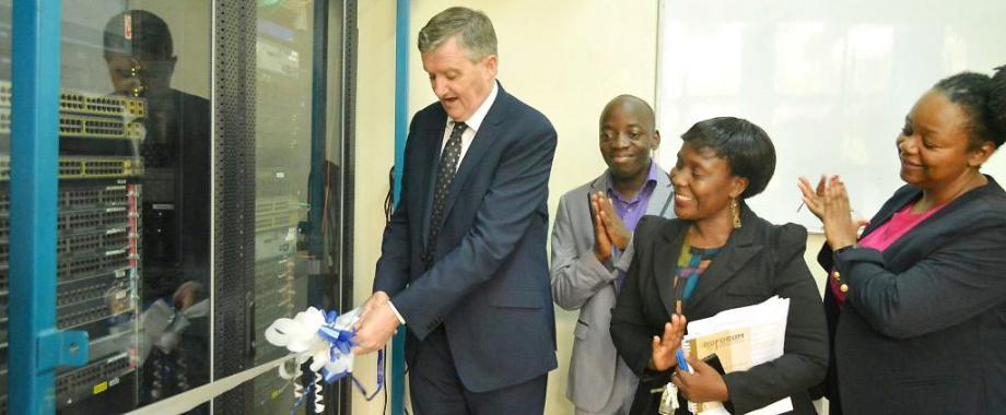 The Irish Ambassador to Uganda, H.E. William Carlos (Left) cuts the tape to mark the official launch of four new innovation labs under netLabs!UG as Deputy Principal CEDAT-Dr. Venny Nakazibwe (2nd R), PI netLabs!Ug- Eng. Dr. Dorothy Okello (R) and a netLabs!UG official applaud, 10th April 2019, Makerere University, Kampala Uganda