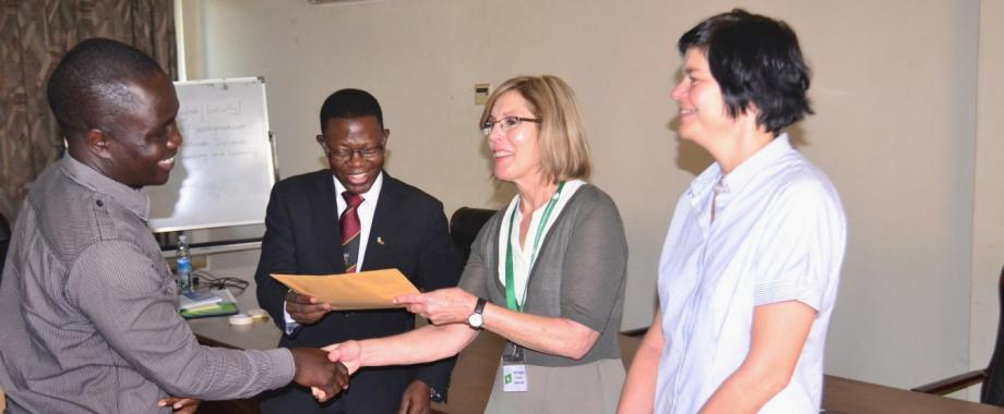 One of the participants (L) receives his certificate from Prof. Mukadasi Buyinza, Director DRGT (2nd L), Prof. Magda Fourie-Malherbe (2nd R) and Dr. Sonja Strydom both from Stellenbosch University at the closing ceremony, 15th Sept 2016, Makerere University, Kampala Uganda