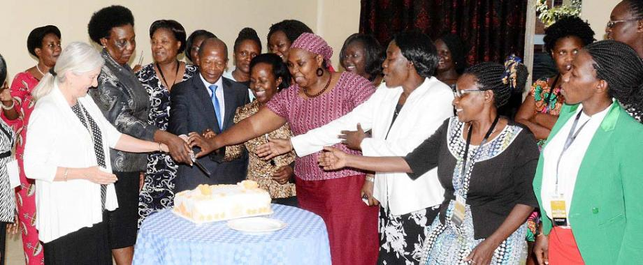 Guest of Honour-Hon. Dr. John Chrysostom Muyingo (3rd L) is joined by Dr. Euzobia Mugisha Baine (5th L), Ms. Naomi Lumutenga (2nd L), Prof. Catherine Hawkins (L) and other facilitators and participants to cut the HERS-EA Second Academy commemorative cake, 6th July 2018, Grand Global Hotel, Kampala Uganda