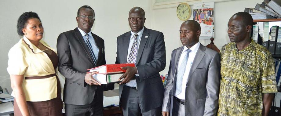 Mr. Benson Barigye (C) symbolically hands over files to the substantive Director, Internal Audit-Mr. Walter Yorac Nono (2nd L) as L-R: Ms. Komugisha Consolate, Mr. Ssanyu Lawrence and Mr. Patrick Akonyet witness during the ceremony held in the Directorate Offices, Main Bulding, Makerere University. Mr. Barigye who served as Acting Director Internal Audit since 6th March 2017 oversaw the implementation of serveral innovations and doubling of the Directorate's annual budget.