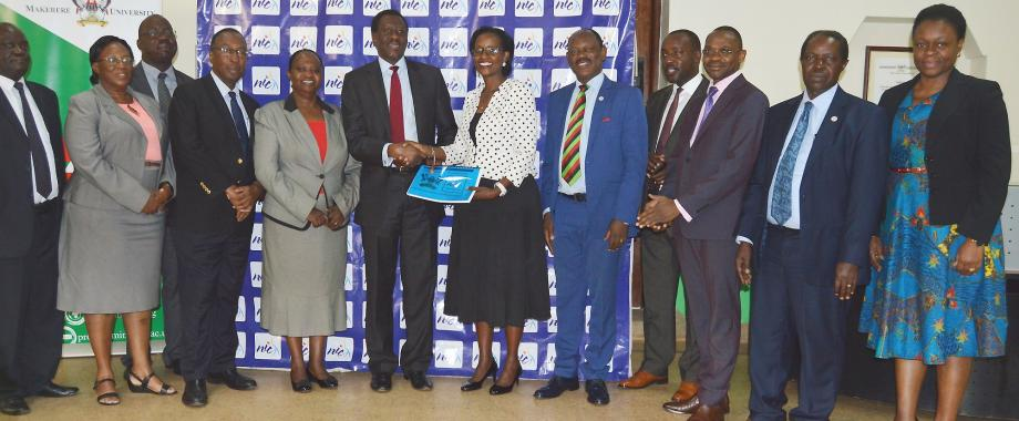 The Chairperson of Council-Mrs. Lorna Magara (6th Right) receives documentation pertaining to ownership of Plot 2A Kampala Road from the Managing Director NIC-Mr. Bayo Folayan (6th Left) as Members of the NIC Boad (Left) and Members of Council and Management (Right) witness on 10th July 2019, Makerere University, Kampala Uganda.