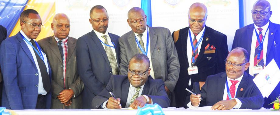 Seated: Mak Vice Chancellor-Prof. Barnabas Nawangwe (R), MKU Vice Chancellor-Prof. Stanley Waudo (2nd R), Standing: Deputy Principal CHS-Assoc. Prof. Isaac Okullo (R), Ag. Director Legal Affairs-Mr. Goddy Muhumuza (2nd R) and other MKU Officials at the MoU signing, 19th September 2017, Mount Kenya University, Nairobi Kenya
