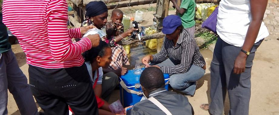 Researchers from AfriWatSan consortium testing the quality of water from a shallow well in Lukaya Town, Uganda. Image:Royal Society