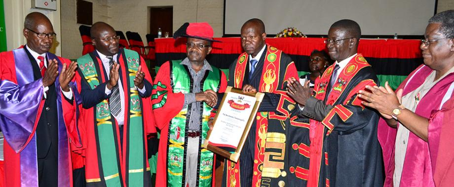 The Chairperson Inaugural Committee- Prof. Elly Sabiiti (L), Acting Deputy Principal-School of Law-Dr. Ronald Naluwairo (2nd),Prof. Ben Twinomugisha (3rdL) receiving a certificate from Dr. Okello Ogwang after presentation of the inaugural lecture.